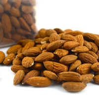 A pile of almonds on a white background with a jar of almonds in the background